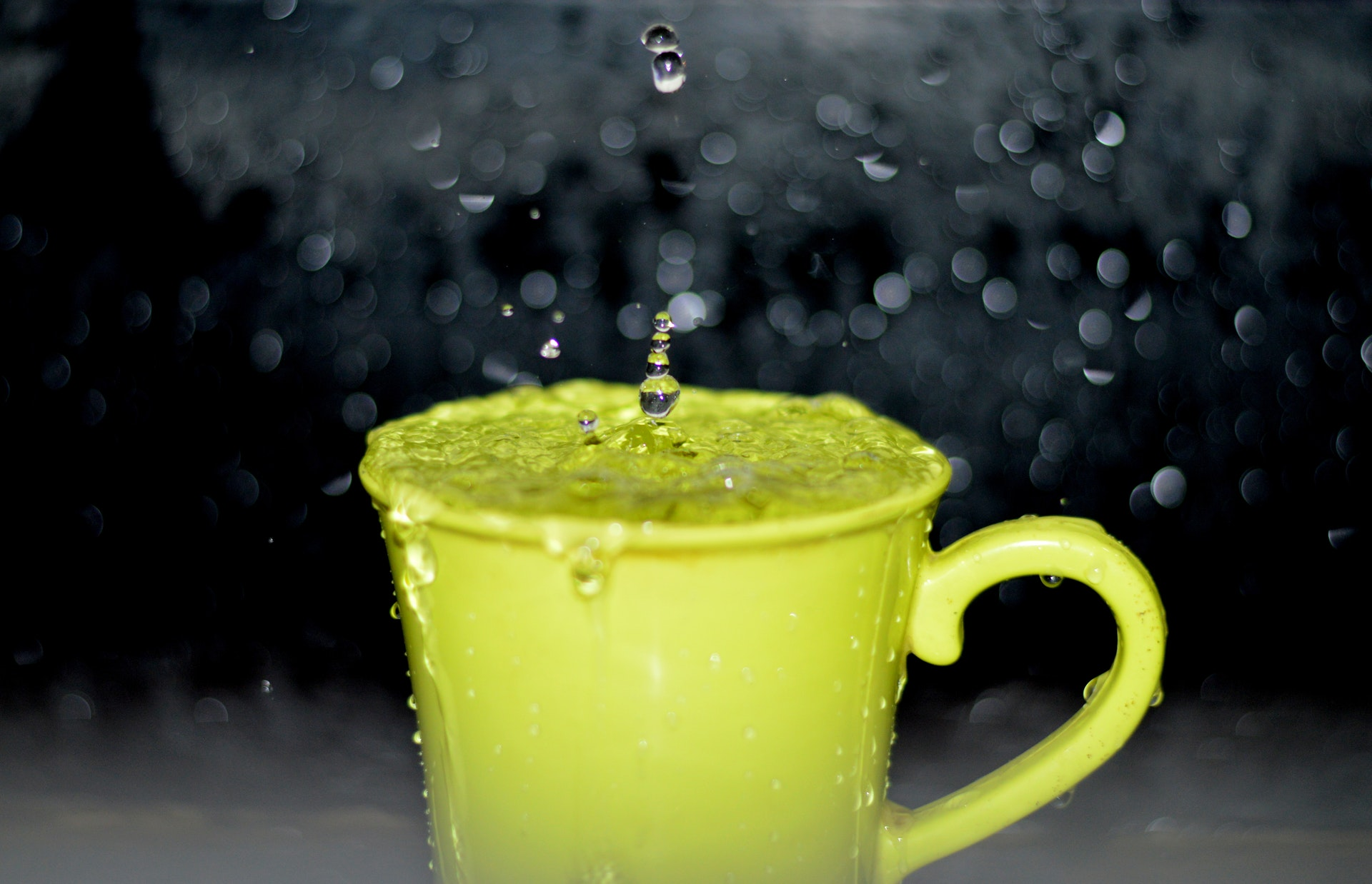 Green cup overfilled and spilling